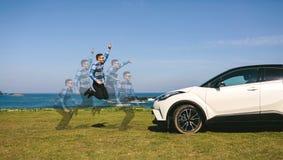 Salto do homem novo feliz com carro fotografia de stock