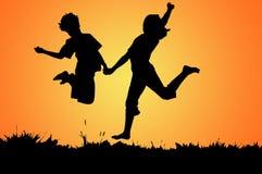 Salto do menino e do gir Foto de Stock Royalty Free