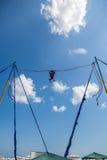 Salto do tirante com mola da moça alto acima no ar com céu azul e nuvens Imagens de Stock Royalty Free