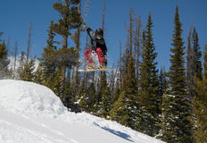 Salto do truque da snowboarding do homem no salto da neve da montanha Fotos de Stock Royalty Free