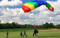 Salto dos Skydivers em tandem imediatamente antes da terra. A equipe de segurança é ao redor ajudar. Foto de Stock