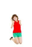 Salto dulce de la muchacha de la alegría que muestra los pulgares para arriba Imagenes de archivo