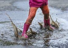 Salto exterior da criança na poça na bota após a chuva imagens de stock