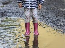 Salto exterior da criança na poça na bota após a chuva fotos de stock