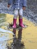 Salto exterior da criança na poça na bota após a chuva foto de stock