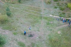 Salto extremo da ponte O homem salta surpreendentemente rapidamente no tirante com mola que salta no parque do c?u explora o dive imagens de stock