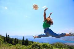 Salto fêmea no ar que joga seu chapéu fotografia de stock