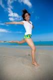 Salto felice alla spiaggia Immagine Stock
