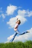 Salto felice della giovane donna Immagine Stock
