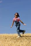 Salto felicemente in un campo. Fotografia Stock