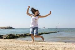 Salto feliz acima da menina na costa imagem de stock