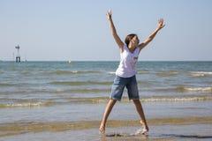 Salto feliz acima da menina na costa imagens de stock