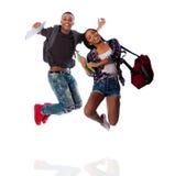 Salto feliz de dos estudiantes de la felicidad Imagen de archivo libre de regalías