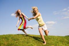 Salto feliz de dos muchachas Fotos de archivo libres de regalías