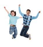 Salto feliz de dos niños Foto de archivo