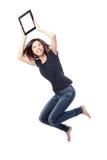 Salto feliz de la belleza joven y mostrar la PC de la tablilla Imagen de archivo libre de regalías