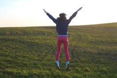 Salto feliz de la muchacha Día hermoso en campo Foto de archivo