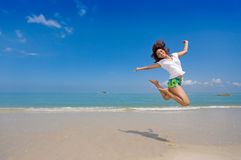 salto feliz de la muchacha en la playa Imágenes de archivo libres de regalías