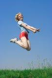 Salto feliz de la mujer joven foto de archivo