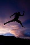Salto feliz de la silueta contra hermoso en puesta del sol Libertad, concepto del disfrute Imagen de archivo libre de regalías