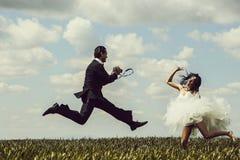 Salto feliz de novia y del novio fotografía de archivo libre de regalías