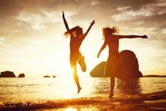 Salto feliz del funcionamiento de la playa de la puesta del sol de dos muchachas imagen de archivo