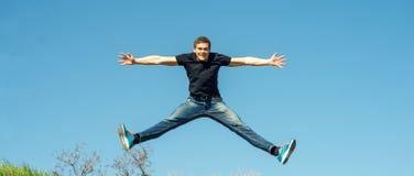 Salto feliz del hombre joven Imágenes de archivo libres de regalías