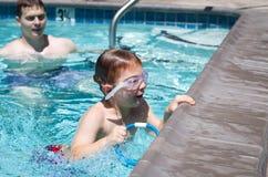 Salto feliz del niño para los aparejos en la piscina Foto de archivo