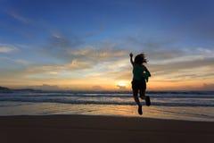 Salto feliz del viajero de la mujer en la playa Imágenes de archivo libres de regalías