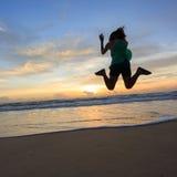 Salto feliz del viajero de la mujer en la playa con salida del sol Fotos de archivo libres de regalías