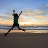 Salto feliz del viajero de la mujer en la playa con salida del sol Imagen de archivo