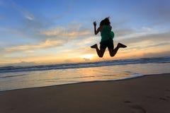 Salto feliz del viajero de la mujer en la playa con salida del sol Imagenes de archivo