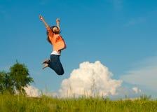 Salto feliz hermoso de la mujer joven en el cielo azul Foto de archivo
