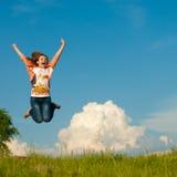 Salto feliz hermoso de la mujer joven en el cielo azul Imagen de archivo libre de regalías