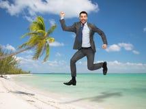 Salto feliz sonriente del hombre de negocios Foto de archivo