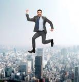 Salto feliz sonriente del hombre de negocios Foto de archivo libre de regalías