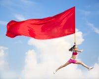 Salto femenino asiático hermoso con la bandera roja grande Foto de archivo libre de regalías