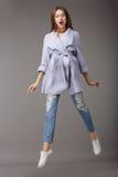 Salto femenino joven de moda en capa azul Imagenes de archivo