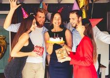 Salto femminile affascinante sulle candele sulla torta di compleanno dopo la fabbricazione del suo desiderio al partito fotografie stock
