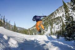 Salto freerider do Snowboarder de uma rampa da neve no sol em um fundo da floresta e das montanhas Imagens de Stock Royalty Free