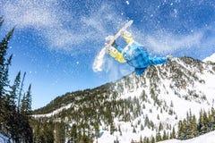 Salto freerider do Snowboarder de uma rampa da neve no sol em um fundo da floresta e das montanhas Foto de Stock