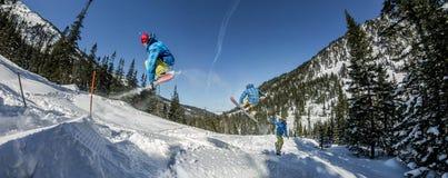 Salto freerider do snowboarder do panorama de uma rampa da neve no sol em um fundo da floresta e das montanhas Imagens de Stock