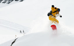 Salto giallo dello snowboarder Fotografia Stock