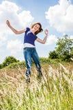 Salto hermoso alegre de la chica joven, bailando en alta hierba seca Foto de archivo libre de regalías
