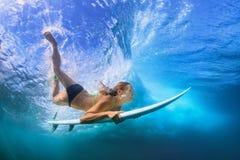 Salto hermoso de la muchacha de la persona que practica surf debajo del agua con el tablero de resaca Imágenes de archivo libres de regalías