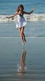 Salto hermoso joven en una playa. Fotografía de archivo