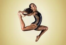 Salto joven de la muchacha del gimnasta Imagenes de archivo