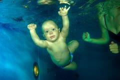 Salto joven del bebé en la piscina Imágenes de archivo libres de regalías