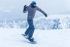 Salto masculino de la snowboard de la snowboard entre en las montañas en snowboard del invierno de la montaña de la nieve imagen de archivo libre de regalías