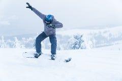 Salto masculino de la snowboard de la snowboard entre en las montañas en snowboard del invierno de la montaña de la nieve imagenes de archivo